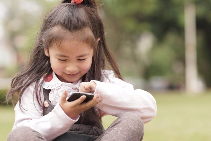 Niño asiático de Taiwan con Smartphone