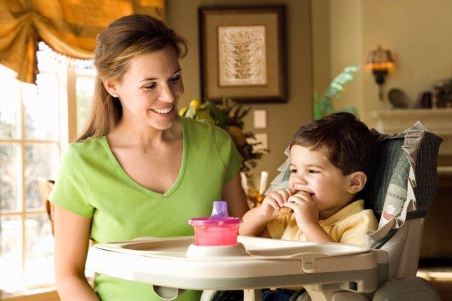 Mamá da de comer a un niño en su trona. Tipos de tronas