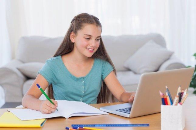 Niña adolescente haciendo deberes en casa con ordenador y libreta