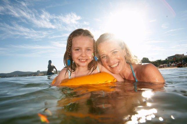 Vacaciones, familia, niña y madre en el mar